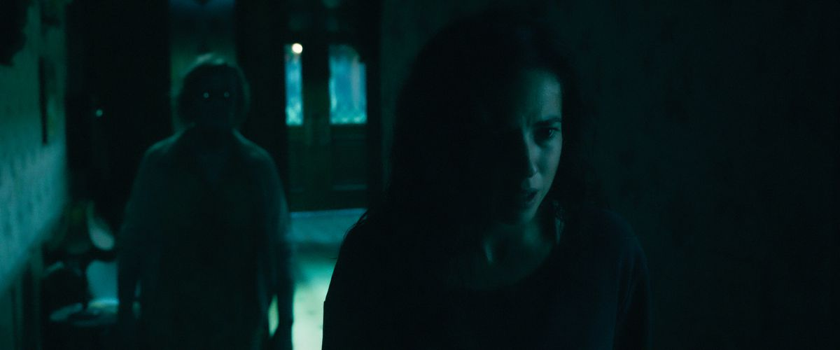 Cristina Rodlo as Ambar is stalked in the dark by a glowing-eyed ghost in No One Gets Out Alive