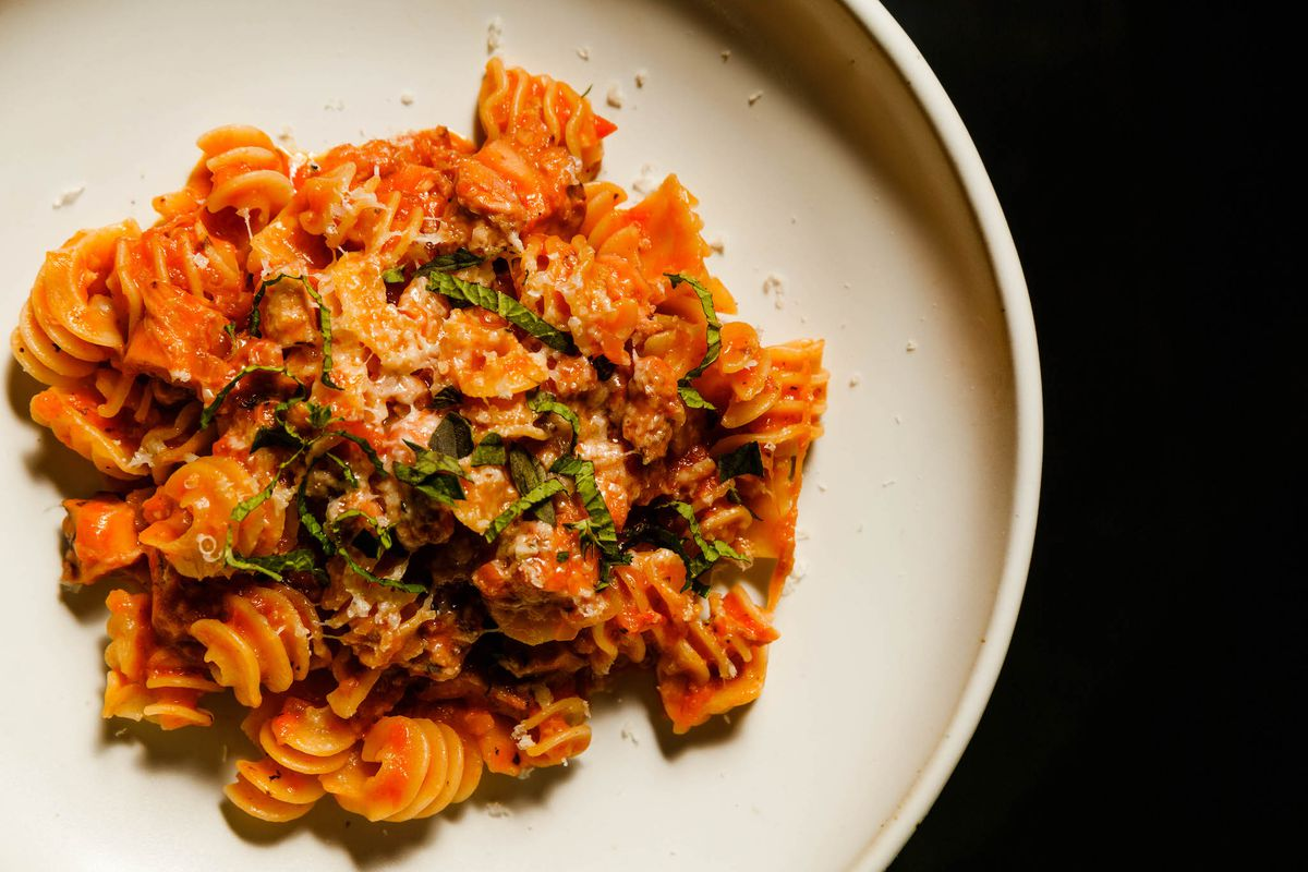 A white plate with ratatore pasta topped with a red sauce and herbs.