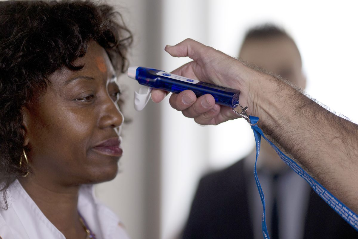 Airport staff test an electronic thermometer.