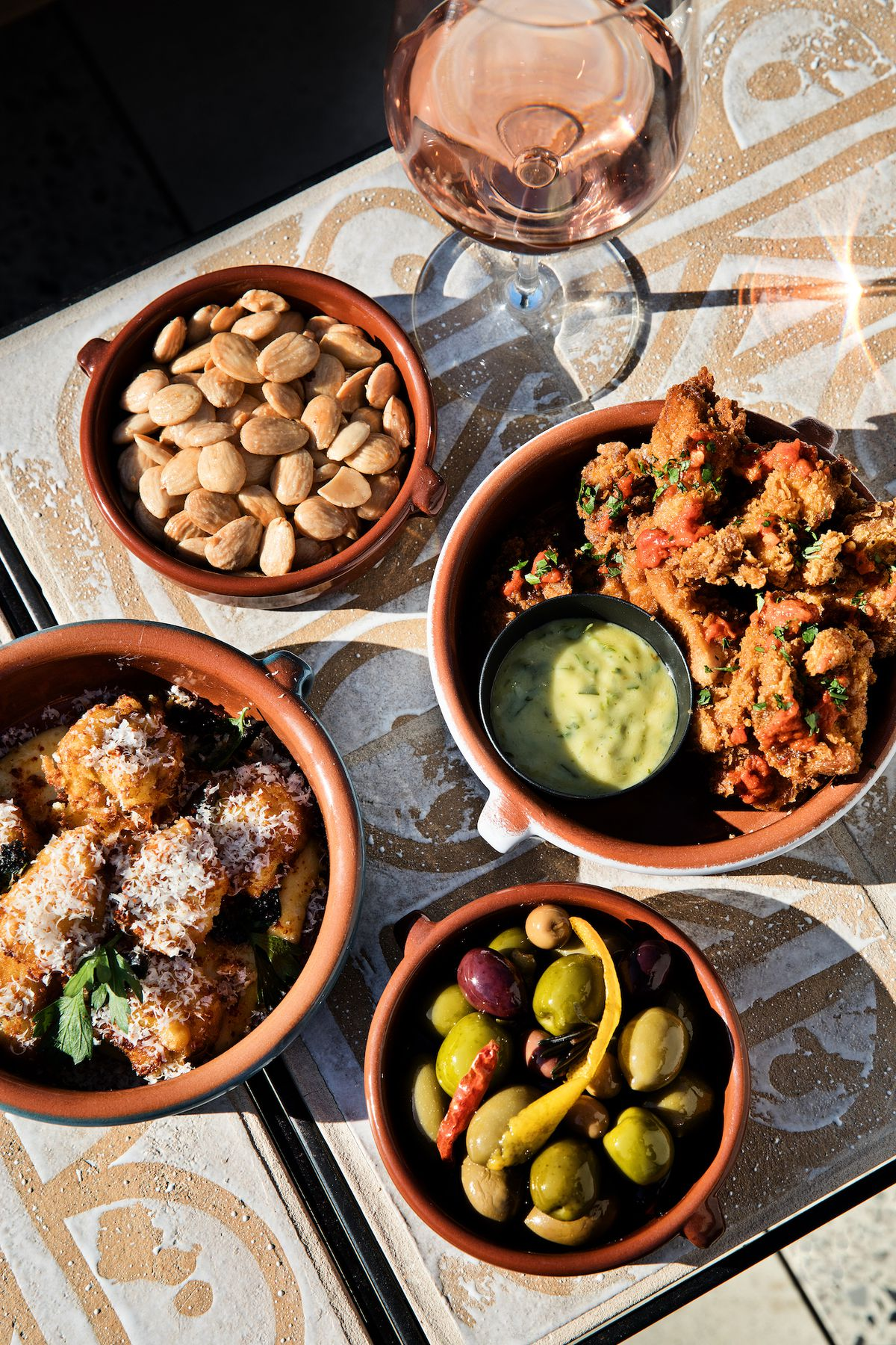 A tilted overhead shot of bowls of fried chicken, almonds, and more on a sunny table.