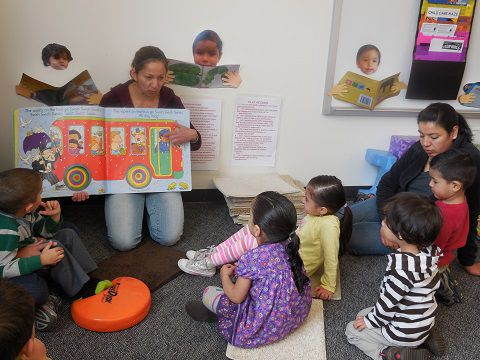 """A parent reads to children in a """"Play and Learn"""" group in northeast Denver. The children all wear the LENA device every few months so their parents or caregivers can get feedback about their verbal interactions."""