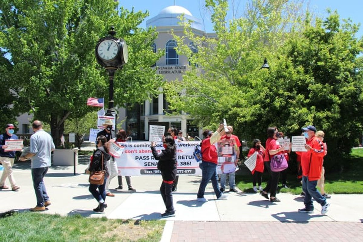 People wearing red T-shirts hold signs in front of a white building