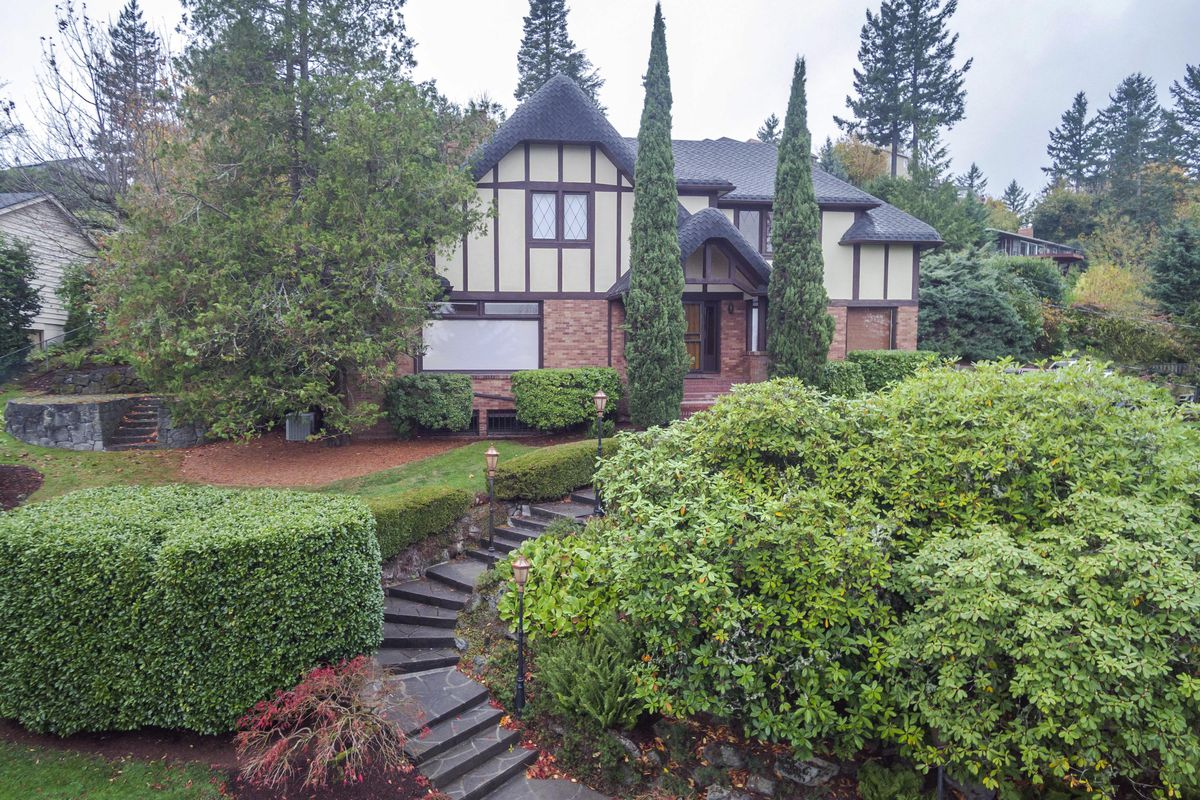 English Tudor style home with brick and stucco walls, with stair pathway leading up to home and hedges and bushes landscaping the front yard.