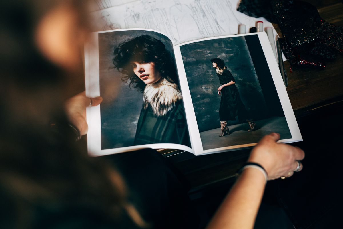 The photographer looks over Noyes's shoulder at her fall lookbook, which shows a model in a green plaid jacket with a fur collar.