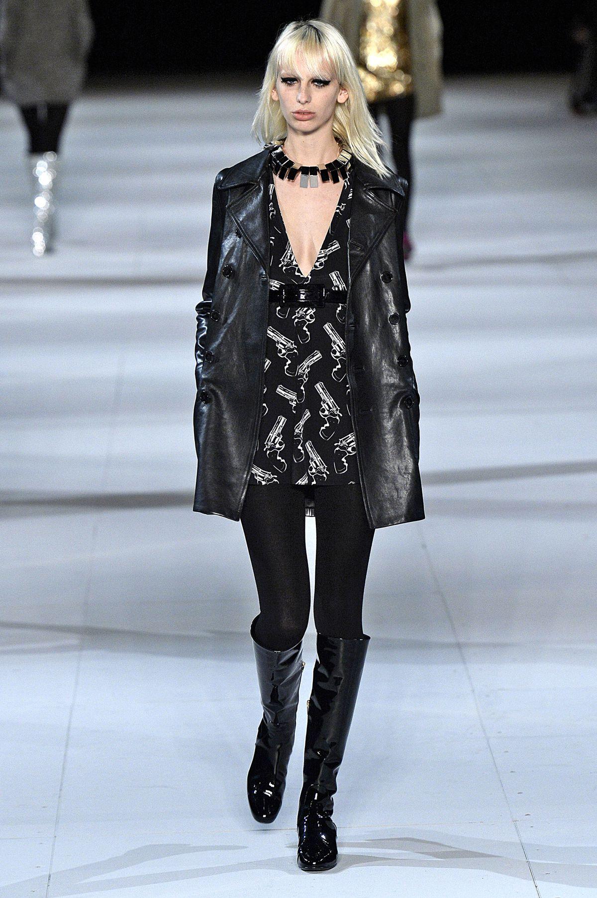 A Saint Laurent model walks the runway in a gun-print shirt.