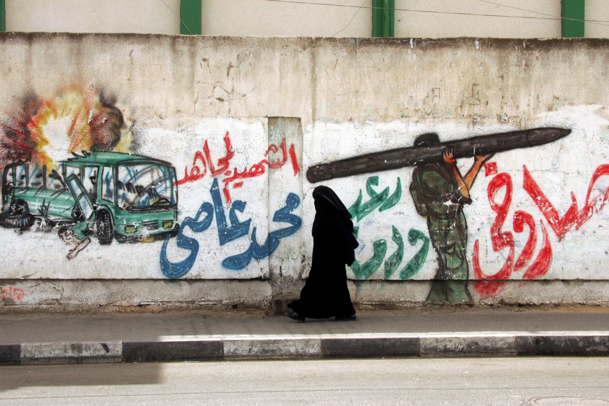 A Palestinian woman walks next to a mural in Gaza City showing an Israeli bus being bombed and a Palestinian militant carrying a rocket