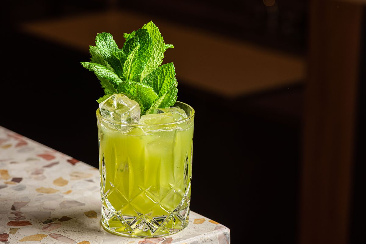 A bright green cocktail in a low tumbler with sprigs of mint reaching to the sky.