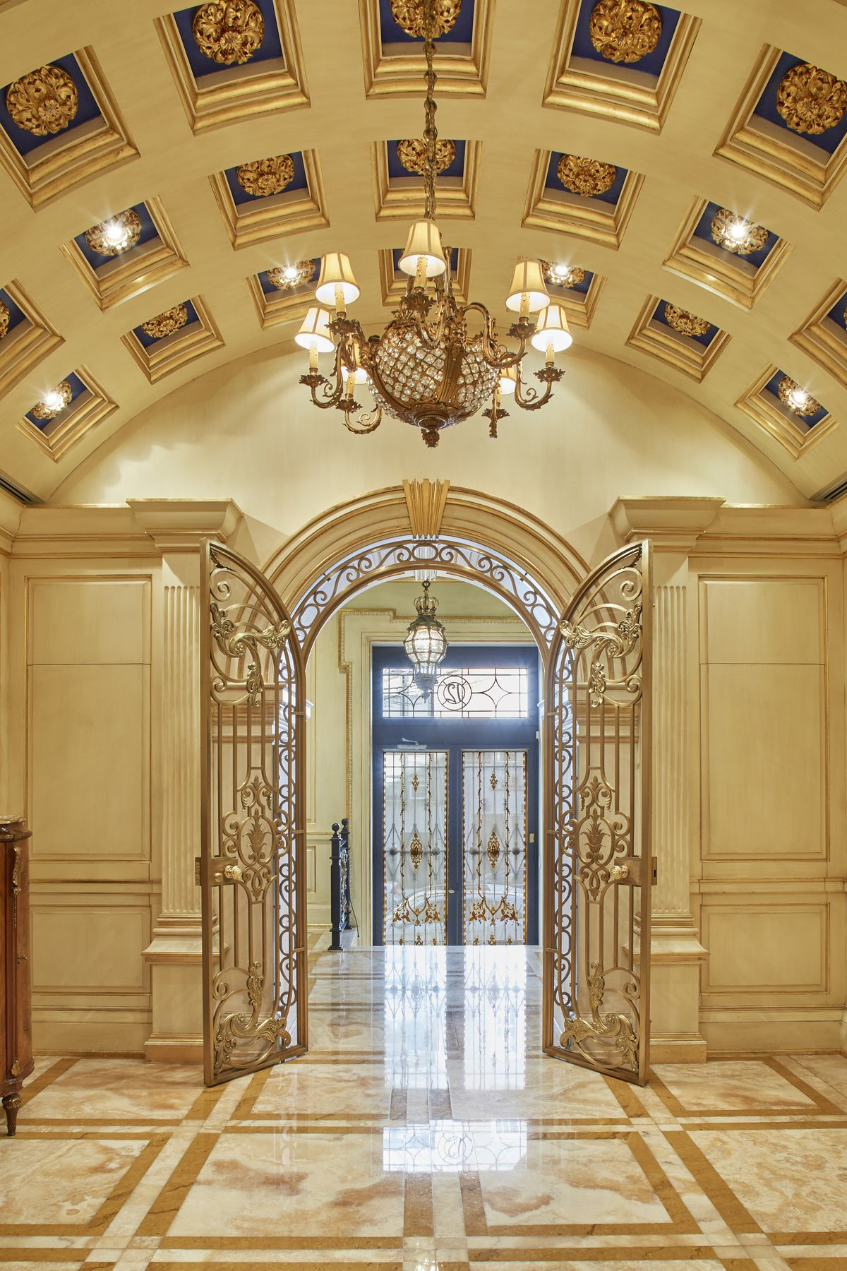 An arched entrance with golden doors, marble floors, and a chandelier.