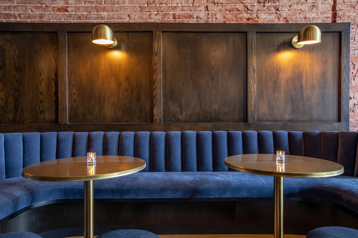 Long blue velvet seating and golden tables with a brick wall behind.