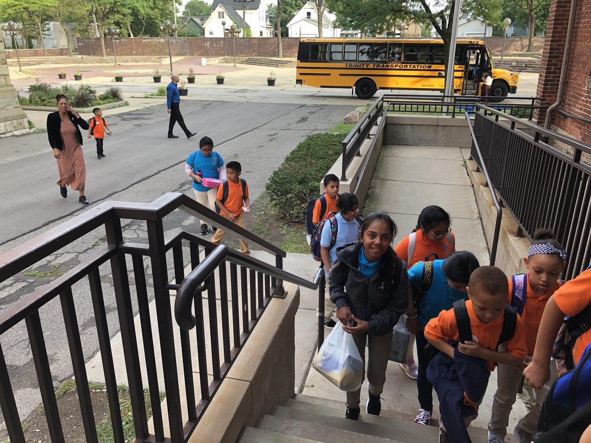 Students file off the bus and into Escuela Avancemos on the first day of school in 2019.