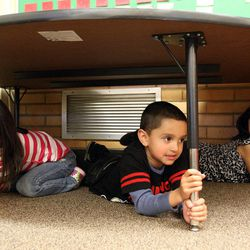 Athziri Valdez-Flores, left, Antonio Gonzalez Navarro, and Ingrid Perez, students in Danielle Wilson's kindergarten class, participate in an earthquake drill at Vista Elementary in Taylorsville, Tuesday, April 17, 2012. This was part of the Great Utah ShakeOut.