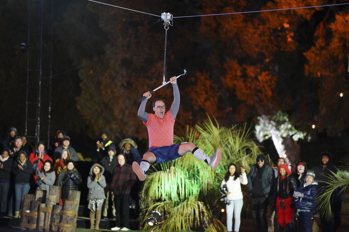 A contestant on Holey Moley ziplines with a golf club
