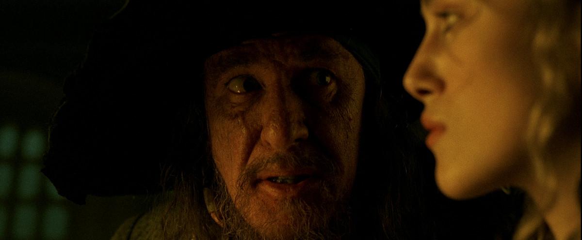 Barbossa (Geoffrey Rush) looks at Elizabeth (Keira Knightley) in profile