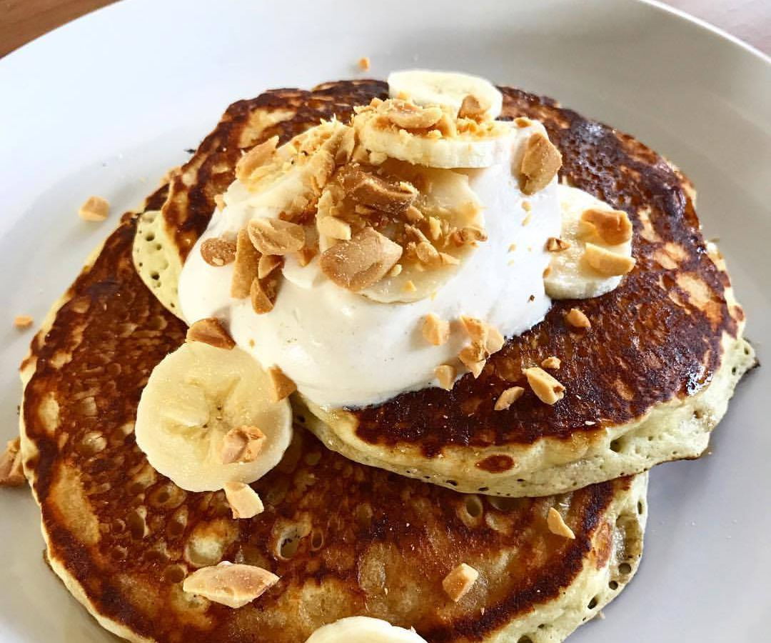 Two thick pancakes stacked on a plate topped with banana slices and brittle