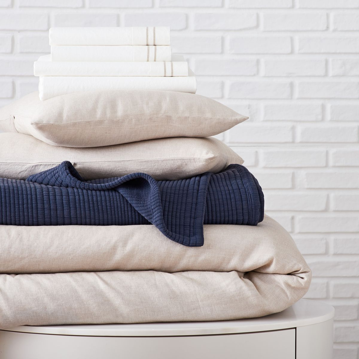 Stack of bedding in neutrals and blues.