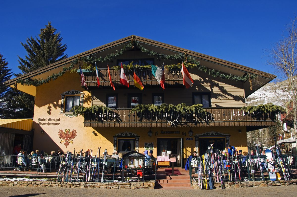 A ski chalet. The exterior is yellow and there are wooden balconies. There are flags hanging from one of the balconies. There are skis leaning against a fence in front of the building.