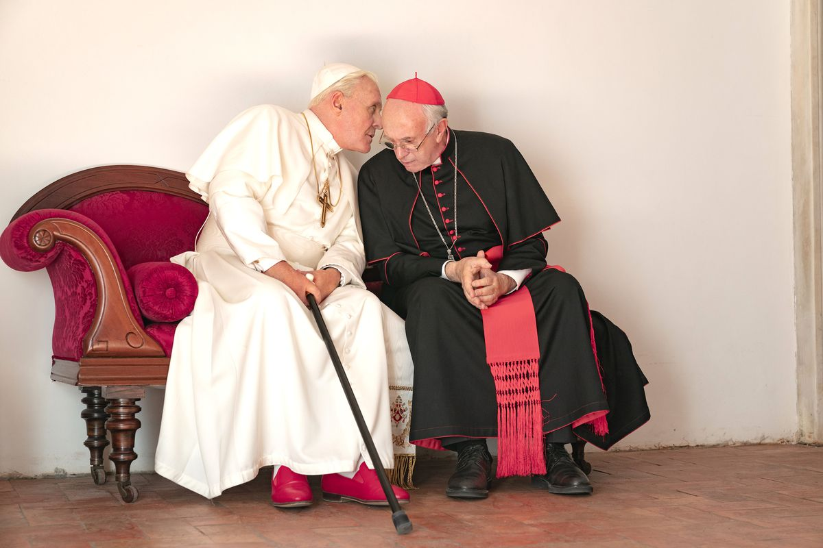 the two popes whisper to each other on a bench