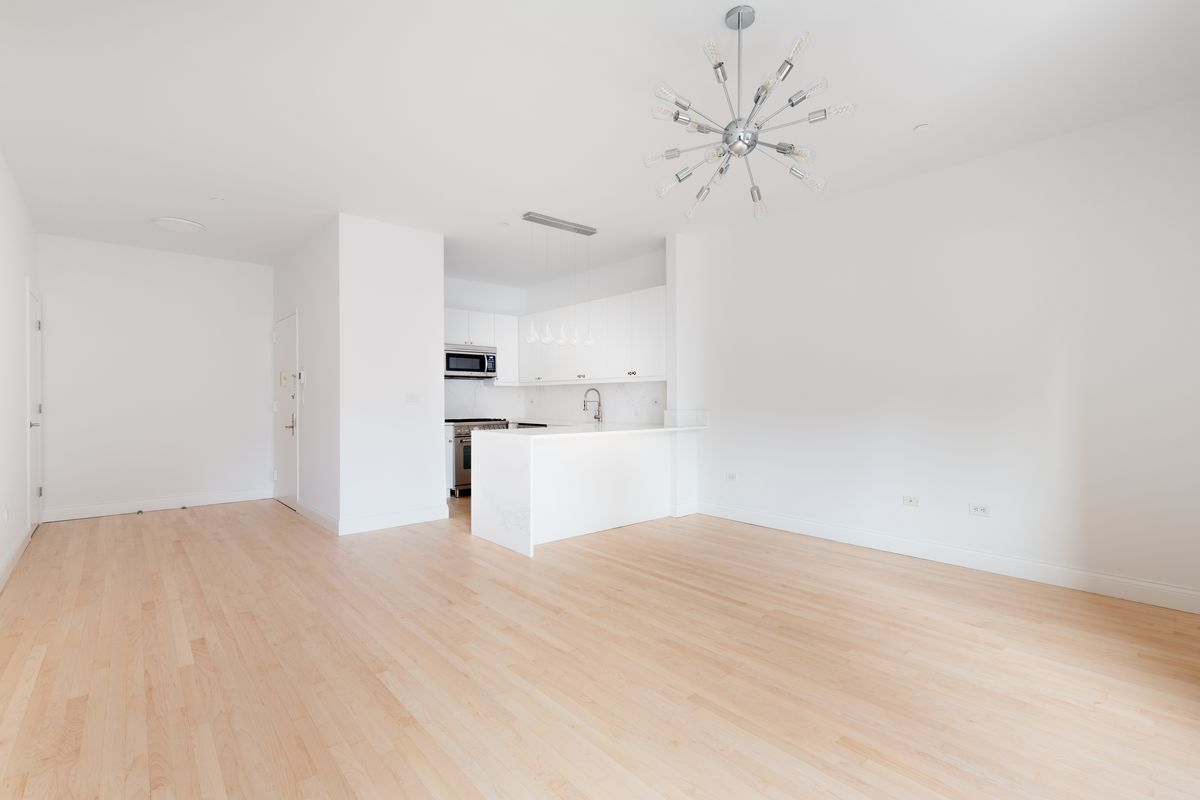 A living area with a silver light fixture, hardwood floors, and white walls.