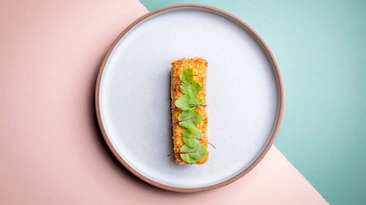 Korroke dish with corn and yellow peppers on a white ceramic plate with a pink and green backdrop.