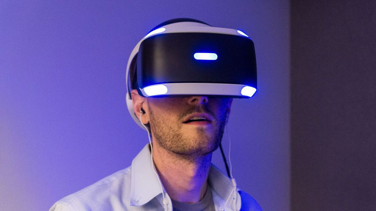 A photograph of a man wearing a PlayStation VR headset, facing the camera