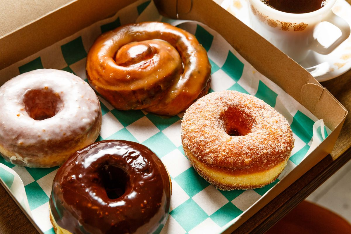 Three doughnuts, one of them covered in chocolate, and a tamarind honey bun sit on a seafoam green and white checkered sheet of paper in an open doughnut box