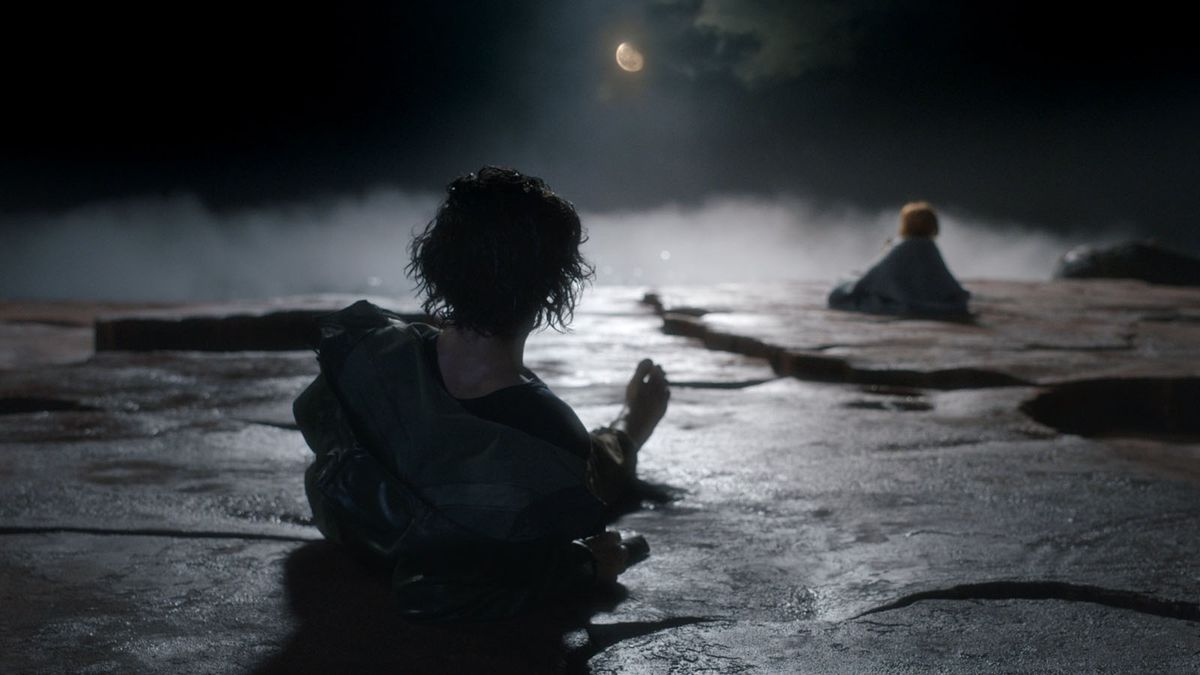 Adam Driver lays on stone, looking at the figure of a young girl, who is singing up at a full moon. It's very dramatically lit.