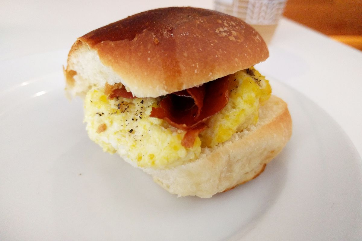 A compact egg and prosciutto sandwich on brioche