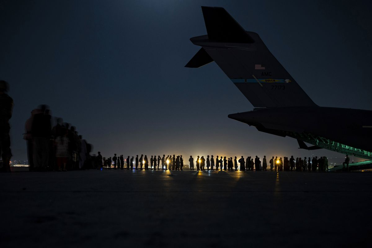 In this image provided by the U.S. Air Force, U.S. Air Force aircrew, assigned to the 816th Expeditionary Airlift Squadron, prepare to load qualified evacuees aboard a U.S. Air Force C-17 Globemaster III aircraft in support of the Afghanistan evacuation at Hamid Karzai International Airport, Kabul, Afghanistan, Saturday, Aug. 21, 2021.