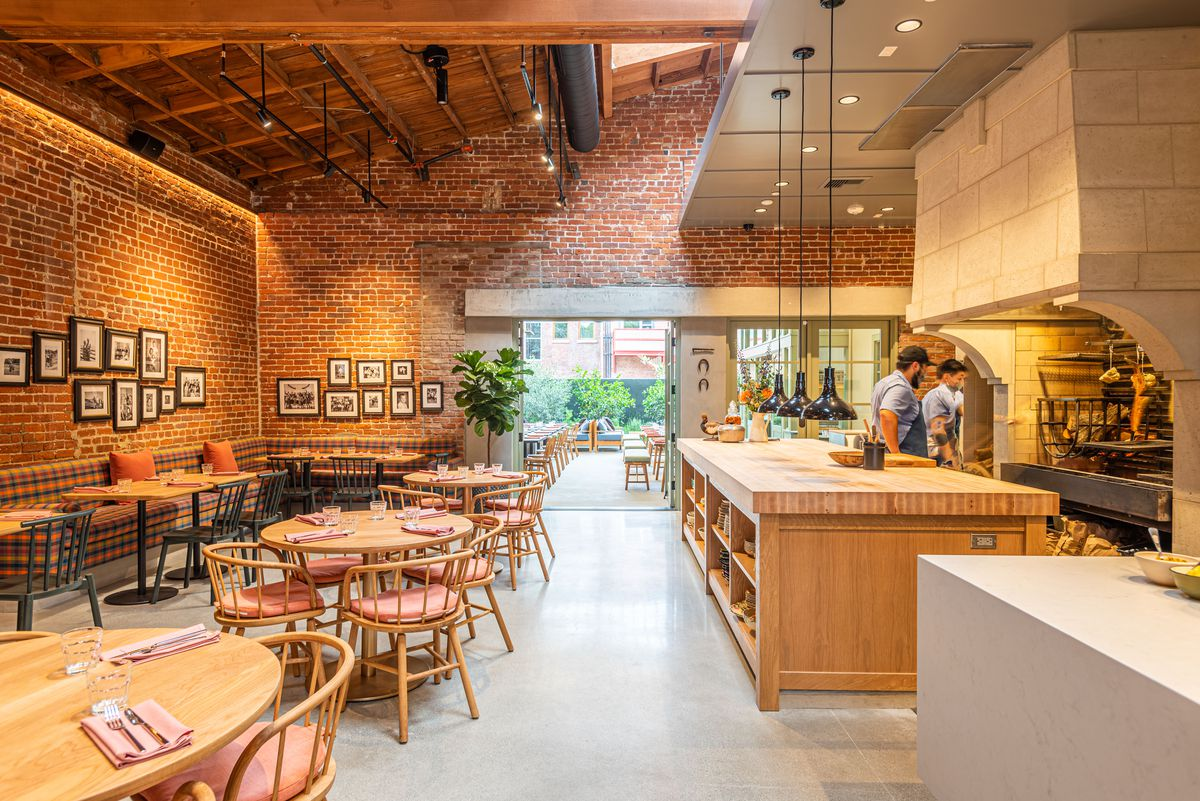 An open restaurant kitchen, at right, with banquette seating and lots of round tables in the middle.