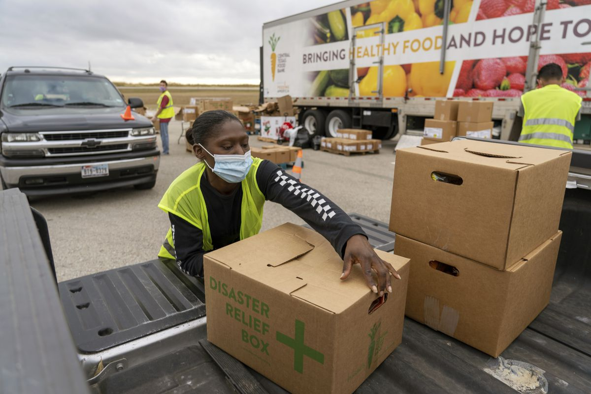 A volunteer loads up a recipient's car at the Central Texas Food Bank