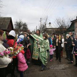 An Orthodox Church priest, center, blesses the faithful holding willow twigs during a Mass to mark the Orthodox Christian Palm Sunday in Minsk, Belarus, on April 5, 2015. In Russia, Ukraine and Belarus, where palms or olive trees don't grow, willow tree twigs are used.
