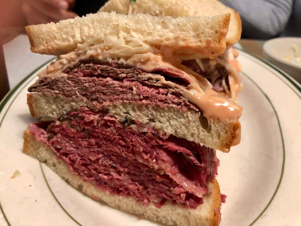A double decker pastrami and corned beef sandwich on rye