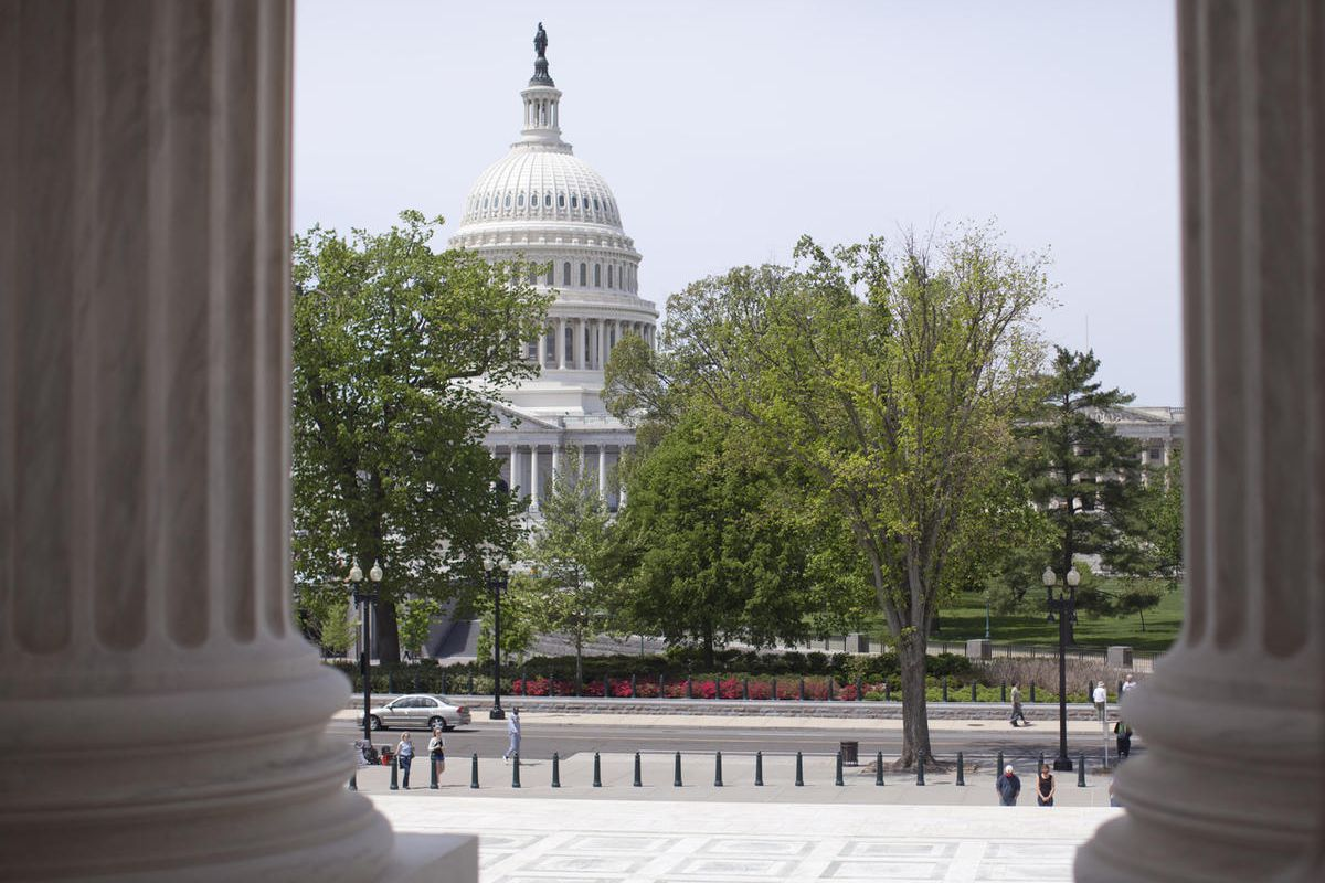 In this May 5, 2014, file photo, the Capitol building is seen through the columns on the steps of the Supreme Court in Washington.