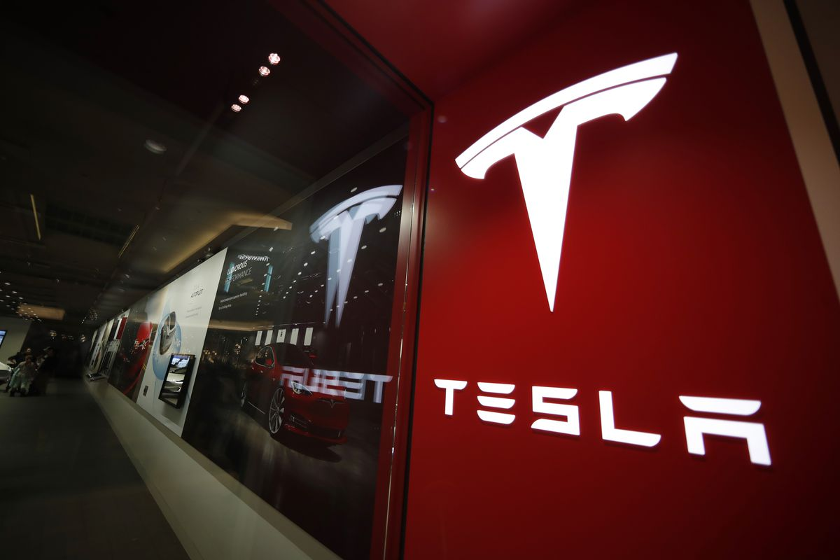 This Feb. 9, 2019, file photo shows a sign bearing the company logo outside a Tesla store in Cherry Creek Mall in Denver. Federal safety regulators have sent a team to investigate the fatal crash of a Tesla electric car near Houston