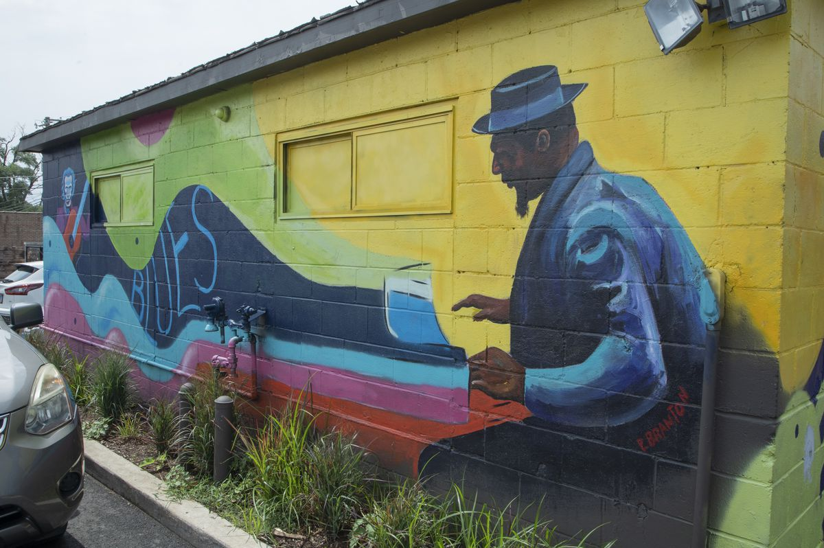 Paul Branton's mural on Nicky's of Beverly's garage was inspired by blues music.  It features a guitarist in one corner and a pianist in another.