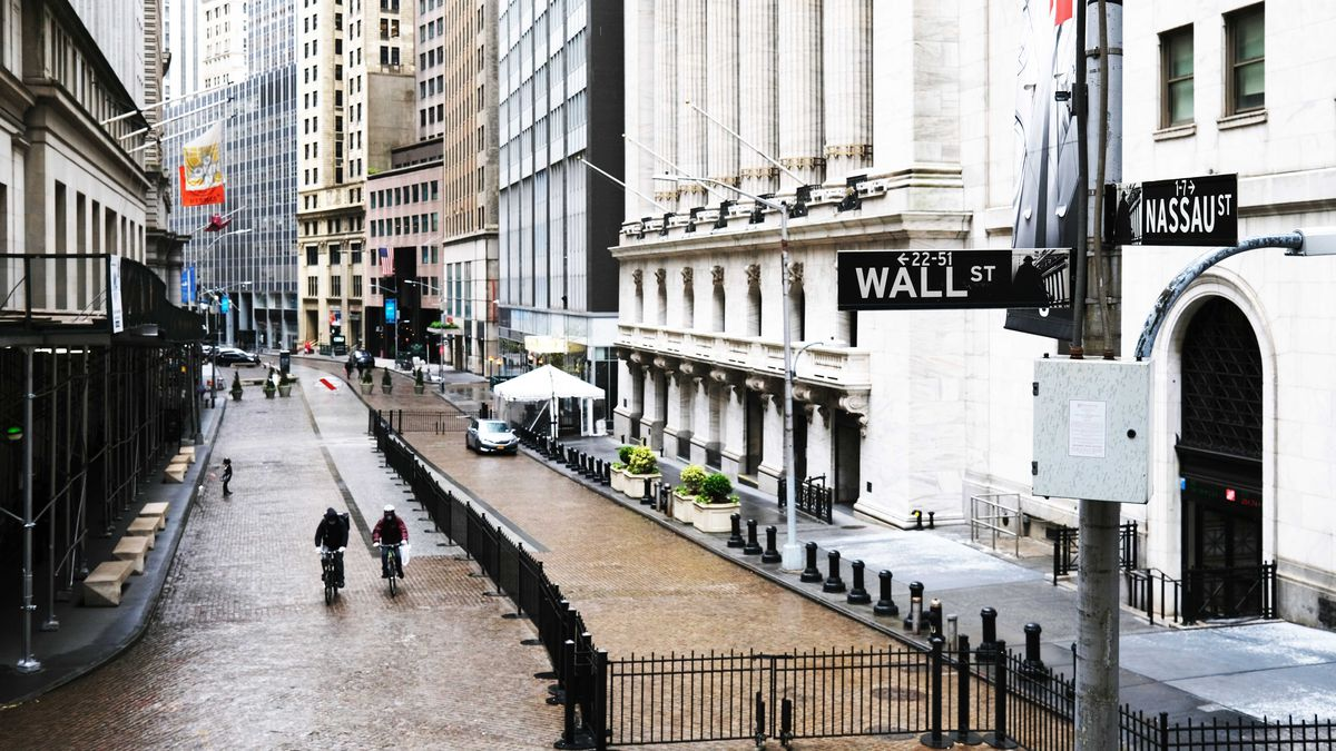 Two people walk in the empty street in front of the Stock Exchange building near the intersection of Wall Street and Nassau Street in New York City on May 8.