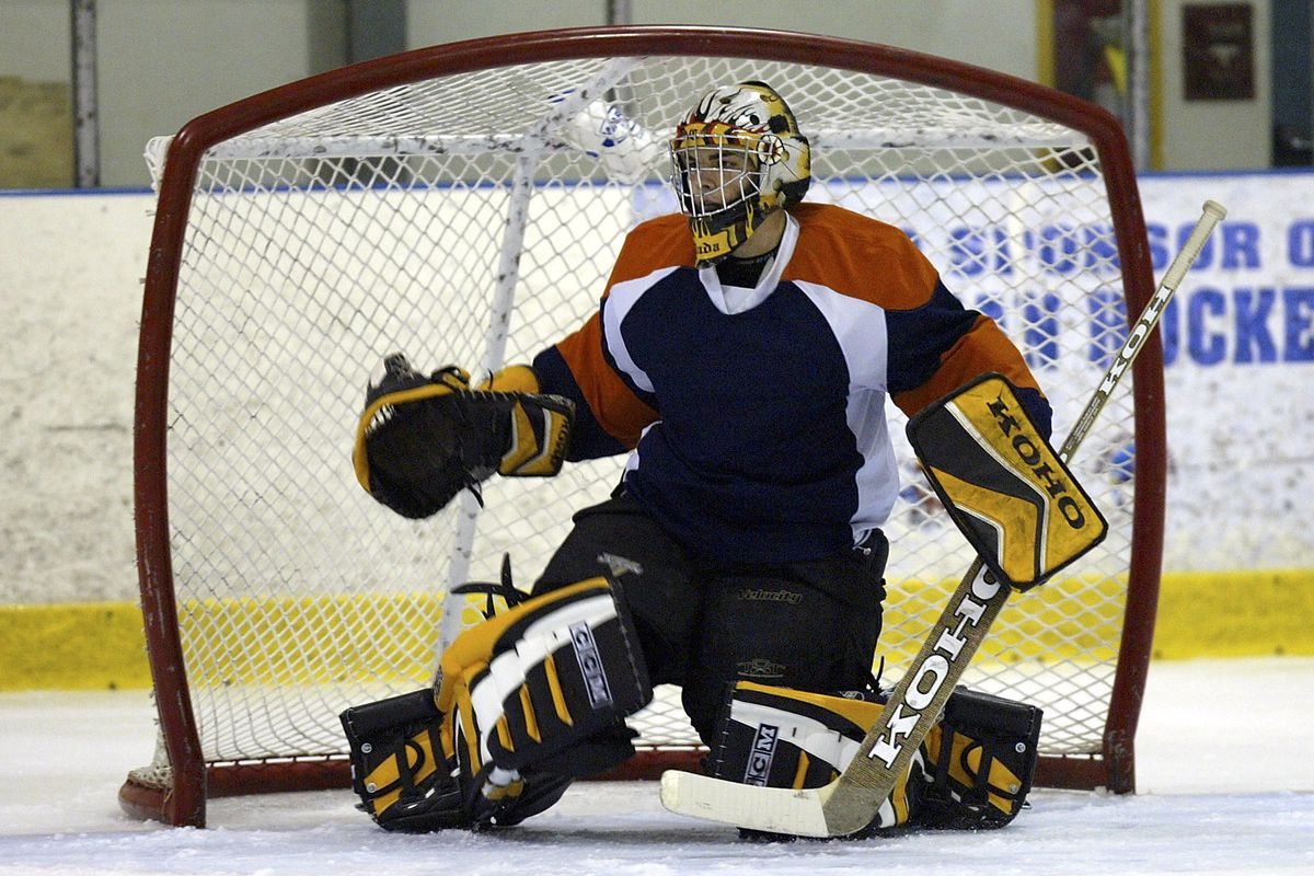 A goalie in smaller equipment tests a larger goal at a Research & Development Camp in 2005.