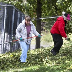 Salt Lake City School District bus drivers Trena Terry, left, and Karen Westover, clean up debris from trees at East High School in Salt Lake City on Wednesday, Sept. 9, 2020. A windstorm that ripped through the Wasatch Front on Tuesday toppled trees and damaged homes.
