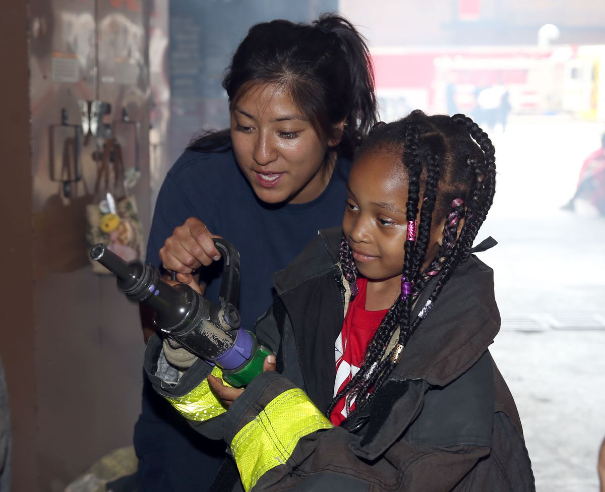 Firefighter Stephanie Iza shows Khalour how to  direct water coming out of the nozzle.