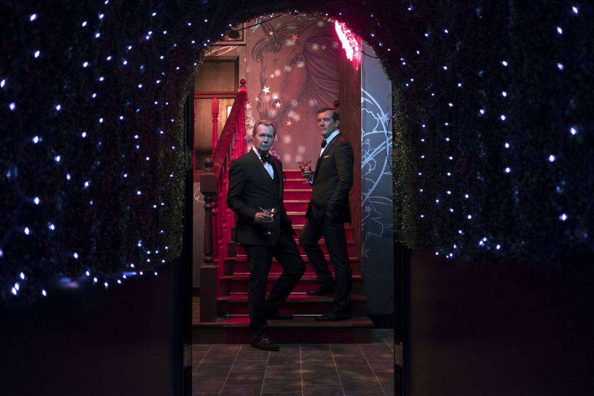 Gary Oldman and Antonio Banderas in slick suits, standing in the stairwell of what looks like a swanky nightclub