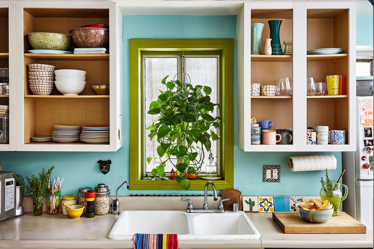 The wall of the kitchen is painted blue. There are cabinets without doors that hold various assorted ceramic bowls, mugs, plates, and vases. There is a window above the sink with a houseplant. The kitchen sink is white and the countertops are tan.