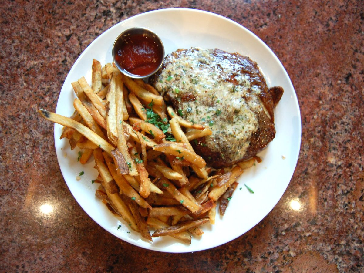 A plate of fries covered in herbs with a container of a sauce and a steak covered in butter