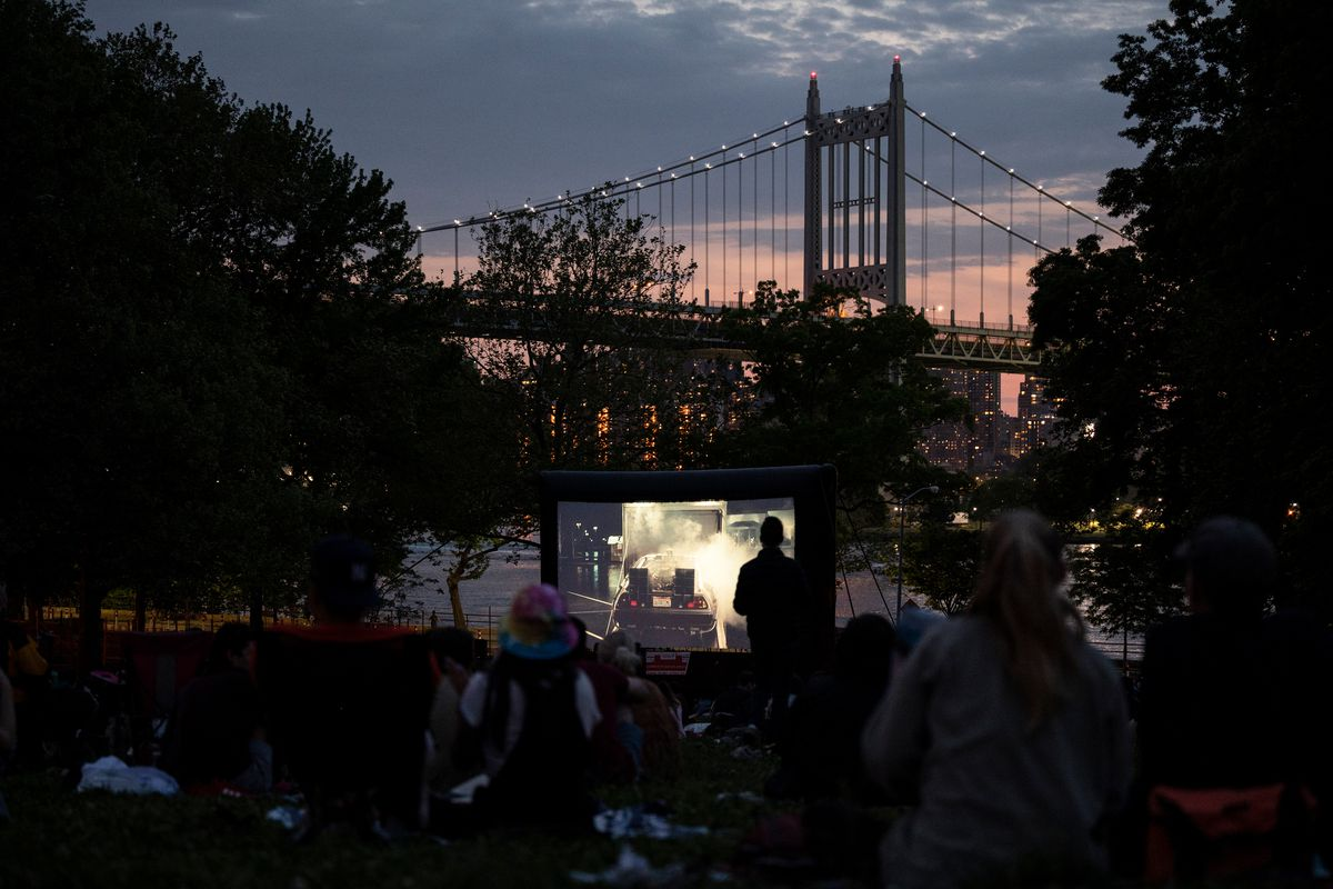 Hundreds of people spread blankets across a field in Astoria Park to watch an outdoor movie, May 27, 2021.