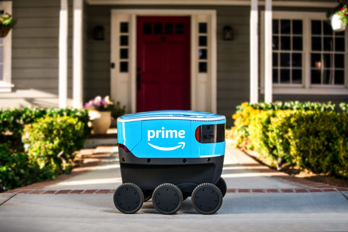 A tiny blue delivery robot with the Amazon Prime logo is seen on the sidewalk in front of a suburban house.