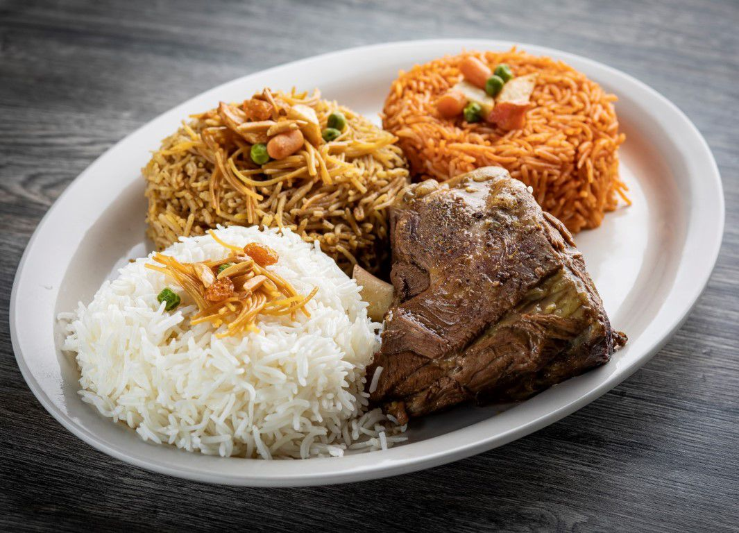 A piece of cooked lamb beside piles of rice
