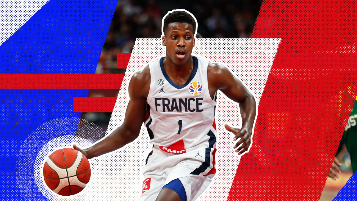 Frank Ntilikina dribbling the ball up the court in a France national team uniform in front of a red, white and blue background.