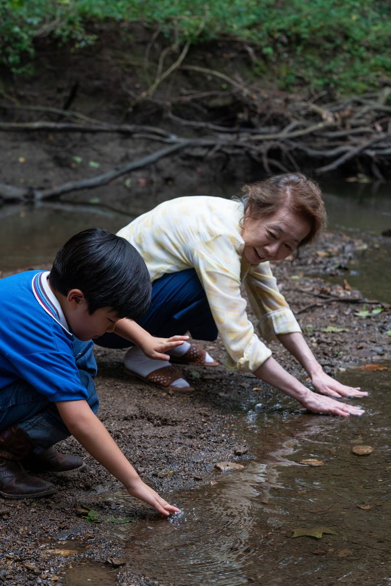 A child and his grandmother crouch at the bank of a stream.