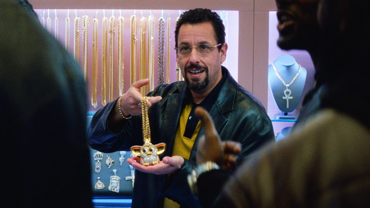 howard holds up a diamond encrusted furby from behind the jewelry shop counter