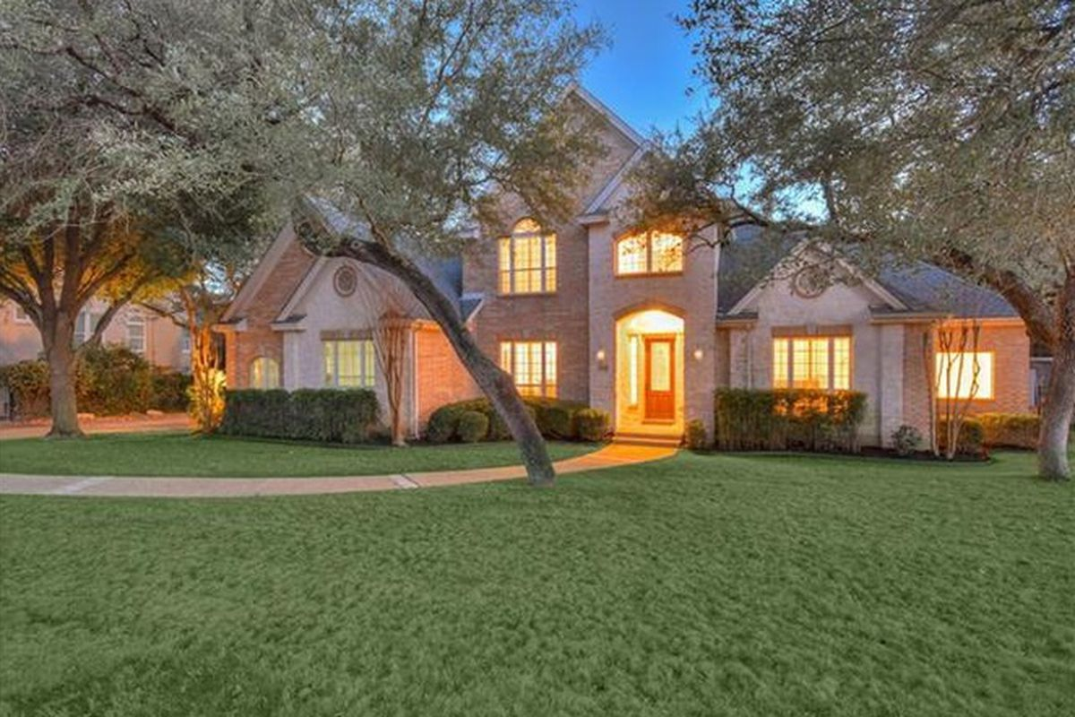 Brick McMansion, traditional style, two stories, evening, lighted inside