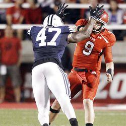 Utah Utes quarterback Jon Hays (9) throws under pressure from Brigham Young Cougars linebacker Ezekiel Ansah (47) in Salt Lake City  Saturday, Sept. 15, 2012.